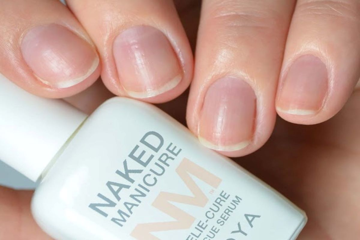 A hand is holding the ZOYA Naked Manicure Rescue Serum as they have the Rescue + Repair System worn on their natural nails.