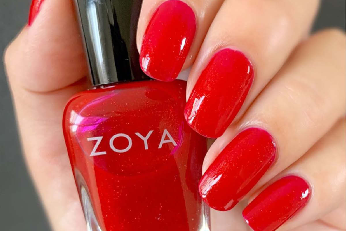 A hand is shown holding a red bottle of ZOYA Nail Polish, with red fingernails wrapped around the bottle.