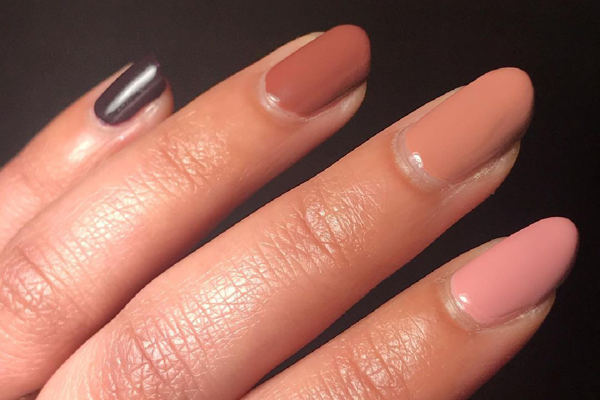 A hand is shown displaying a skittle manicure of different nude polishes by ZOYA.