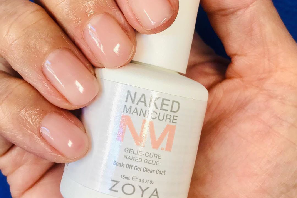 A hand holding ZOYA Naked Gelie with their fingers wrapped around the bottle, showcasing the Gelie-Cure Foundation manicure on their fingernails.