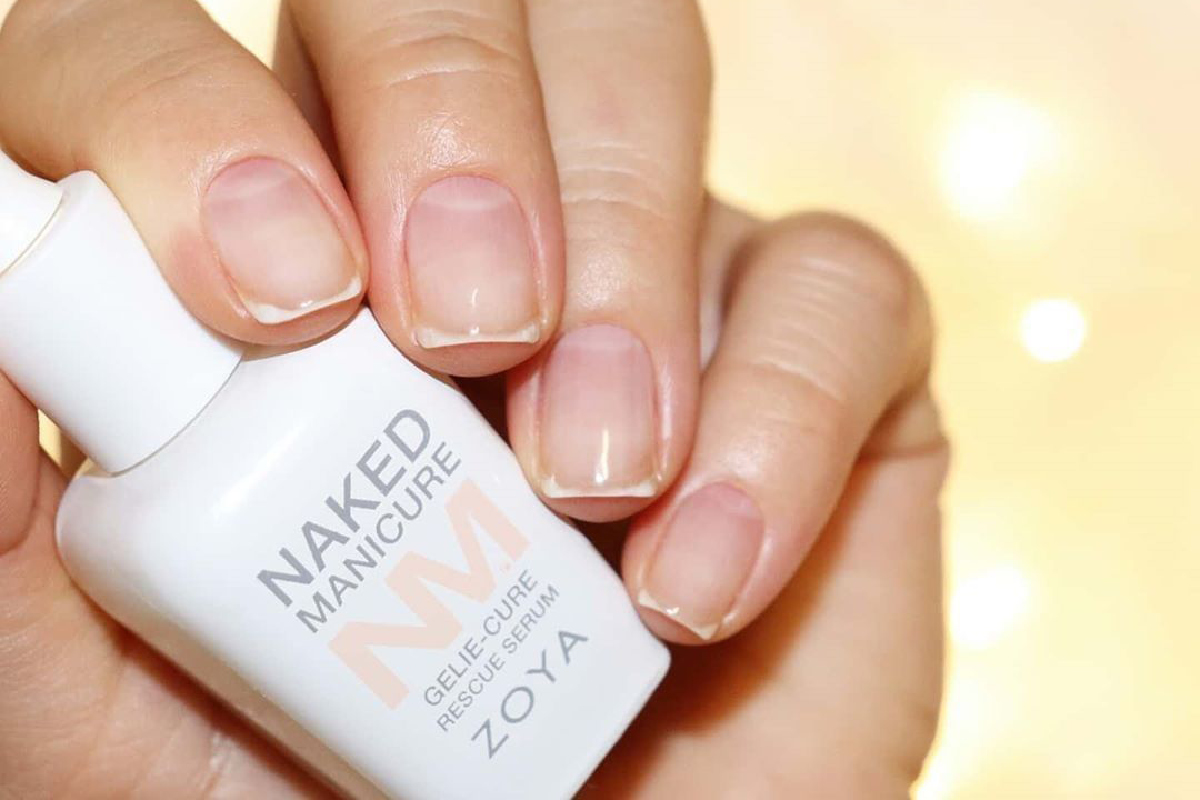 A hand holding the ZOYA Naked Manicure Rescue Serum with their fingers wrapped around the bottle. The Rescue Repair treatment manicure is on their fingernails.