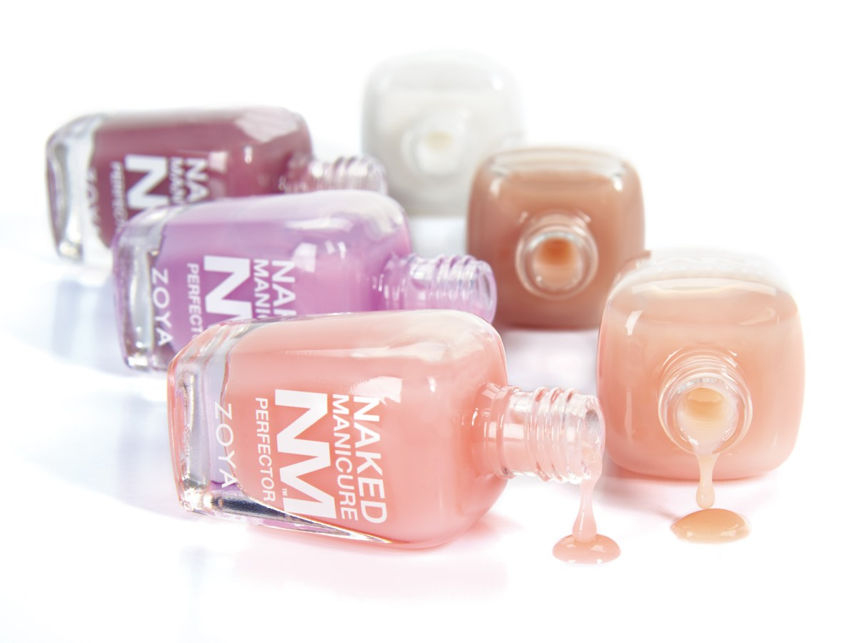 Naked Manicure Perfector bottles are laying on their sides with slight spills.