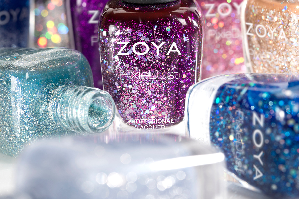 A close-up display of multiple ZOYA PixieDust colors, with some bottles standing and some on their sides.