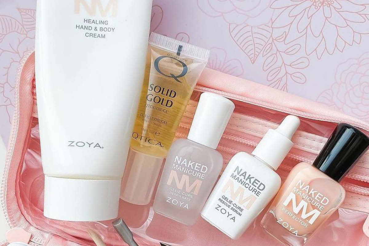 A row of the products mentioned in the article are laying on top of the ZOYA Naked Manicure Gelie-Cure Kit Bag. Products include Naked Manicure Hydrate & Heal Lotion, QTICA Solid Gold Cuticle Oil, Rescue Serum, Repair Base and Naked Perfector.