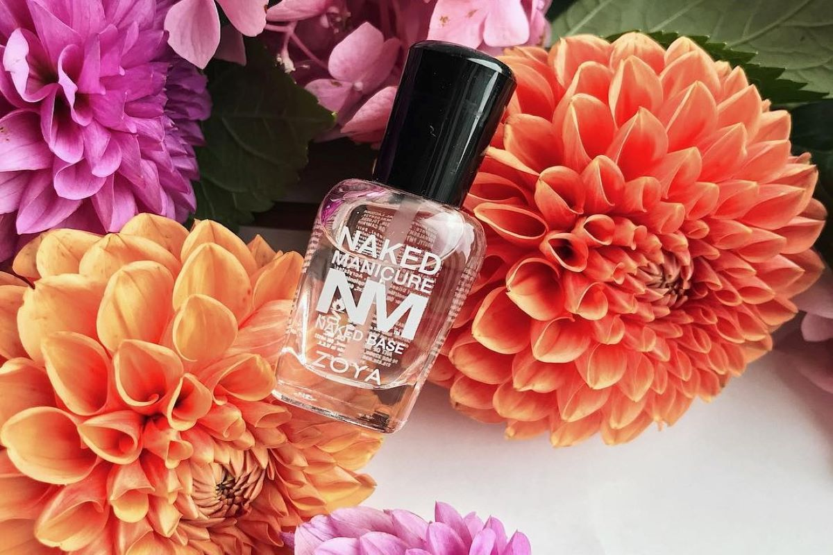 A ZOYA Naked Manicure bottle of Naked Base is resting on a background of colorful flowers.