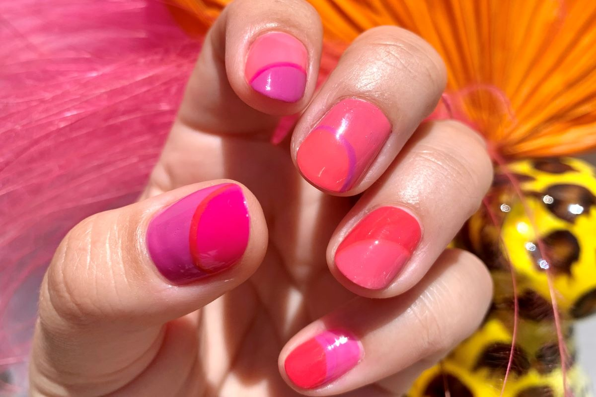 A color block manicure is shown on the nails using the ZOYA Dreamin and Easy Neon Collections. The hand is in front of a colorful background of feathers.