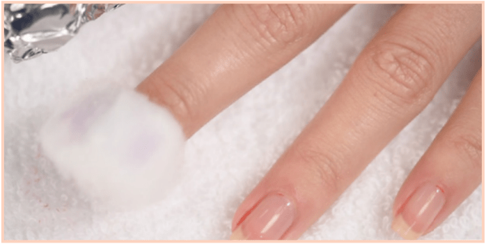 A cotton ball soaked with Remove + rests on a nail to demonstrate step one of the Gelie-Cure System removal process.
