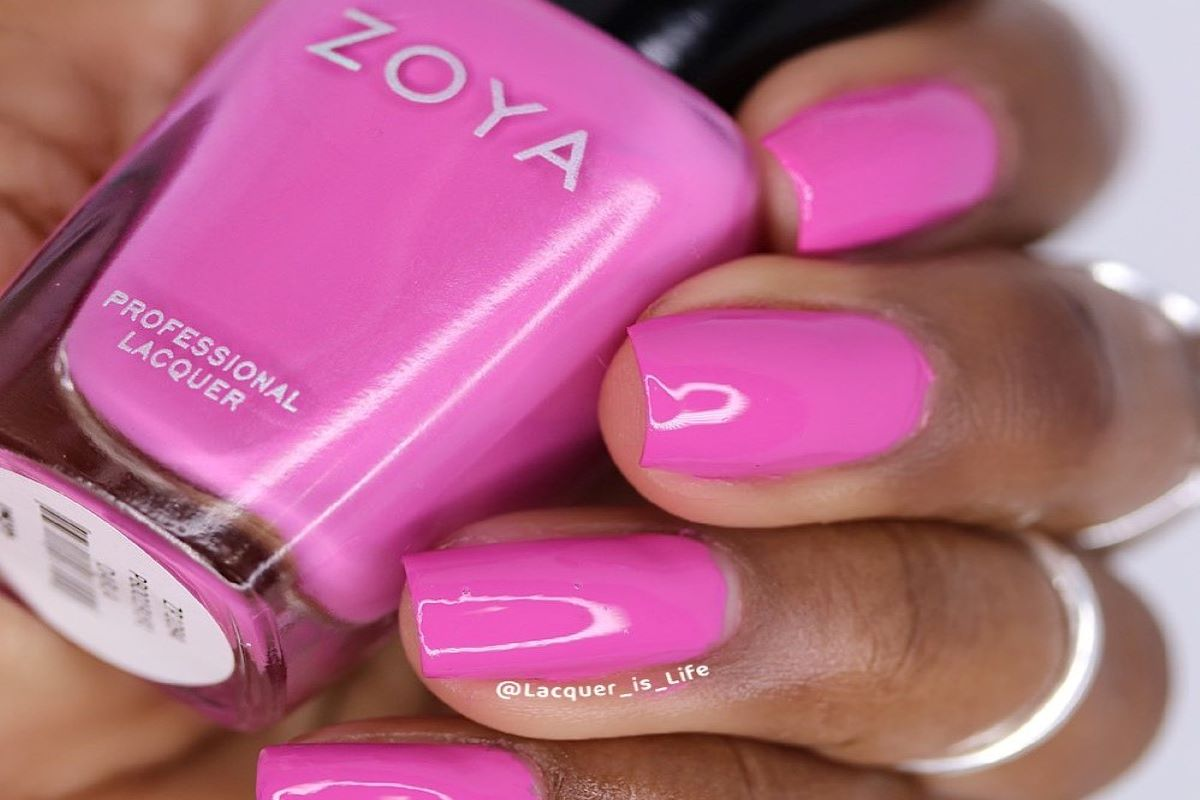 A hand holding a bottle of ZOYA Darla with the color on her nails.