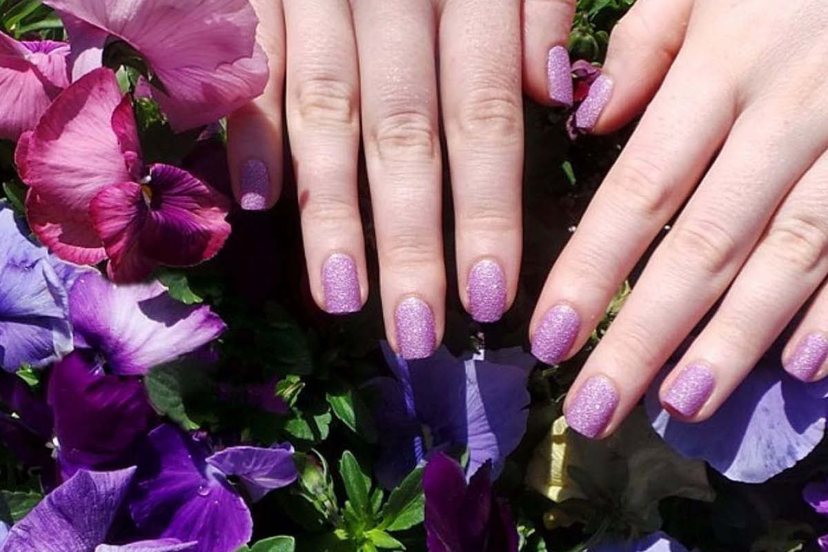 A ZOYA PixieDust shade painted on the nails in a floral background.