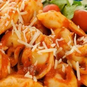 Closeup of a plate of cheese tortellini with marinara sauce