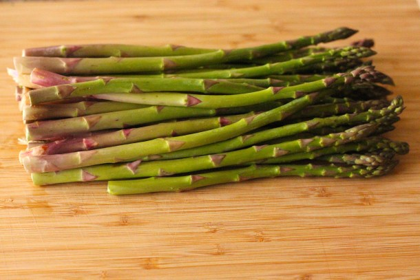 asparagus lined up on a cutting board