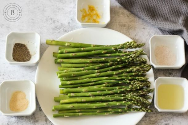asparagus surrounded by spiced in white bowls