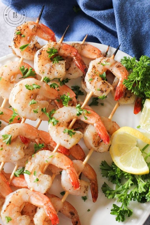 grilled shrimp skewers on a white plate with lemon and parsley