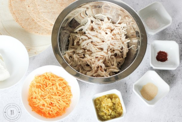Ingredients for chicken taquitos. Shredded chicken, cheese, chiles, spices and cream cheese