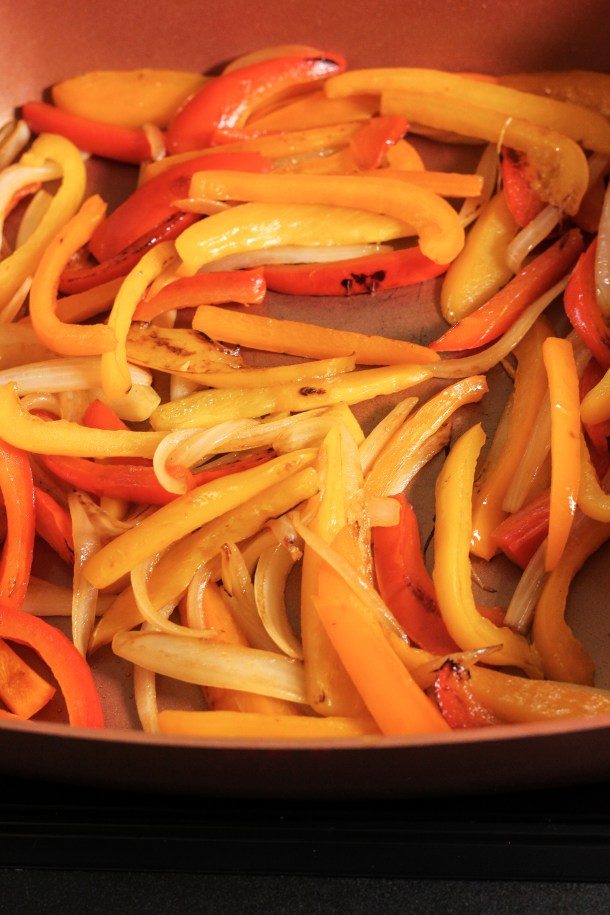 sauteed peppers and onions in a copper pan