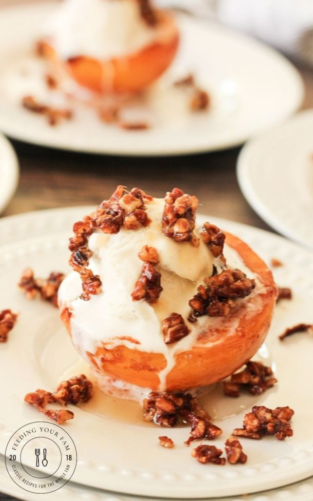 caramelized peaches topped with vanilla ice cream and toasted pecans on a white plate