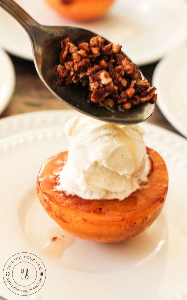 spooning toasted pecans over a caramelized peach topped with vanilla ice cream