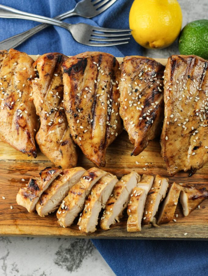 chicken breasts, one sliced on a wooden platter