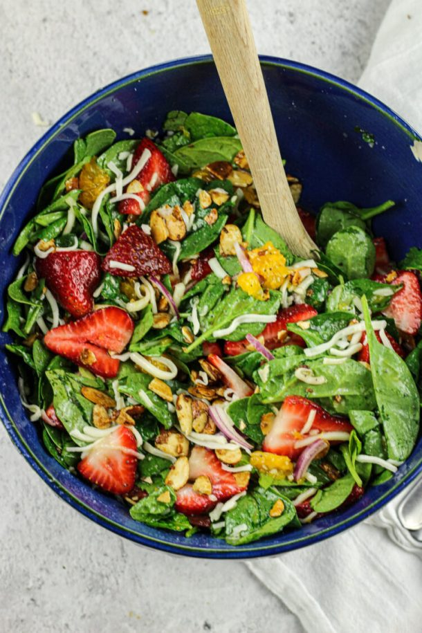 strawberry spinach salad in a blue salad bowl