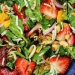 spinach, sliced strawberries, mandarin oranges, mozzarella cheese and toasted almonds in a blue salad bowl