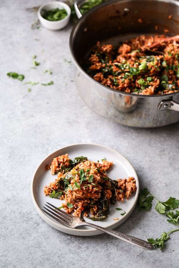 vegan jambalaya with greens in a pot and on a plate