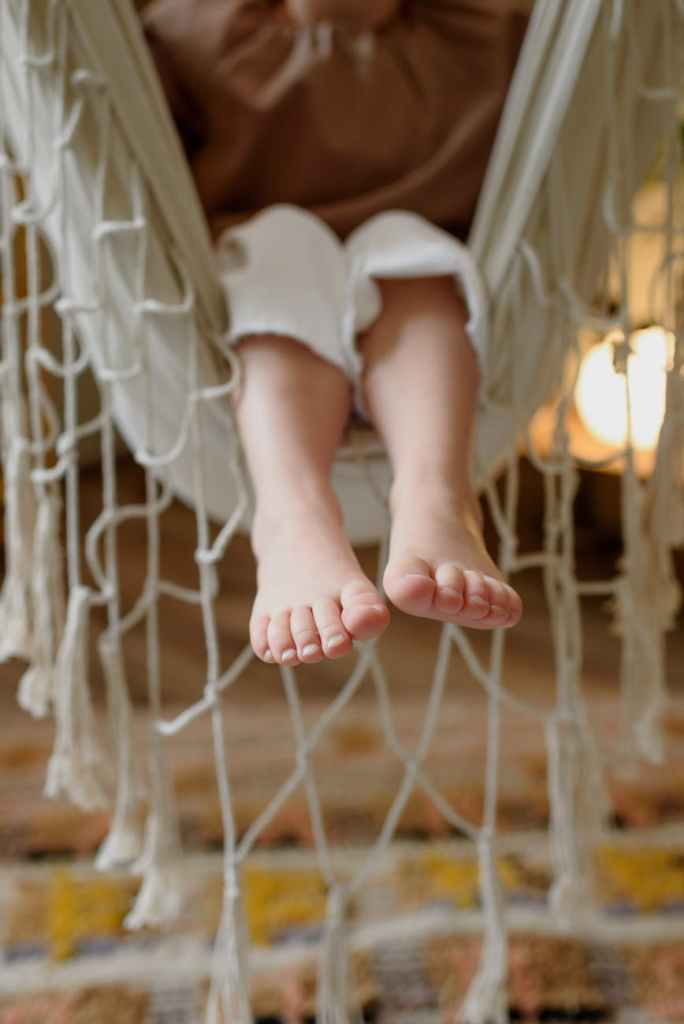 faceless child resting in comfortable hammock in house