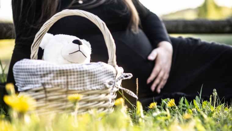 pregnant woman sitting on grass near picnic basket