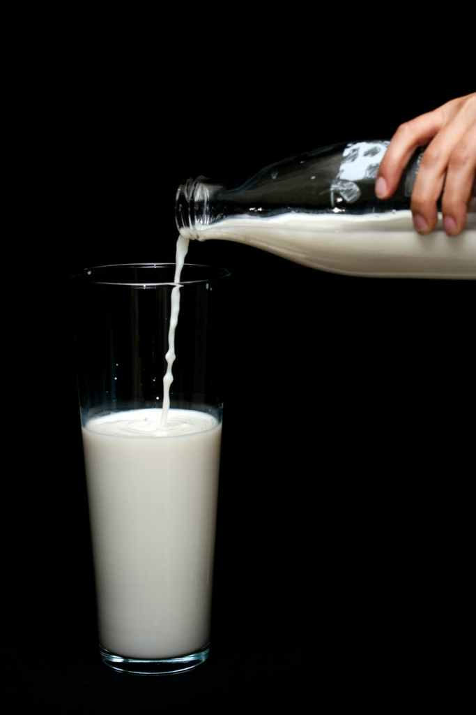 person pouring milk in highball glass