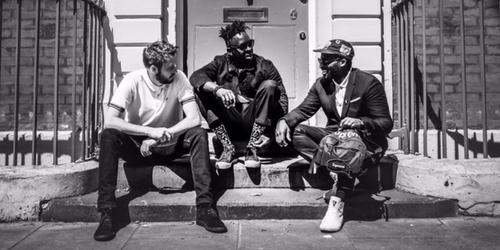 Black and white photo of Cory laughing with two friends whilst sitting on some steps