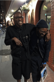 Colour photo of Cory and his friend laughing and hugging whilst walking down the street