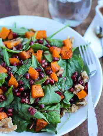 This roasted Butternut Squash Pomegranate Spinach Salad is a hearty salad recipe that is wonderful in the winter & includes simple healthy vegan ingredients