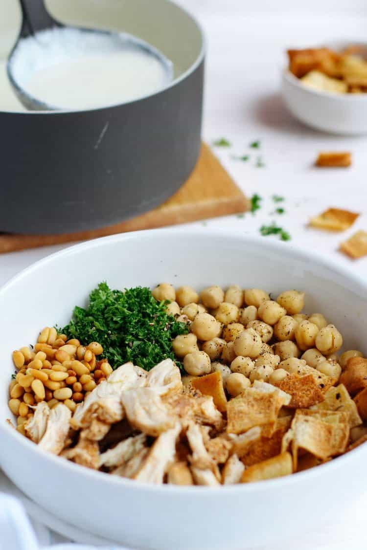 This authentic Lebanese Chicken Fatteh is an amazing combo of flavors made with yogurt, spiced shredded chicken, chickpeas, toasted pine nuts & pita bread!