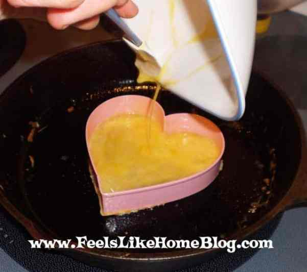 Egg being poured into a heart cookie cutter