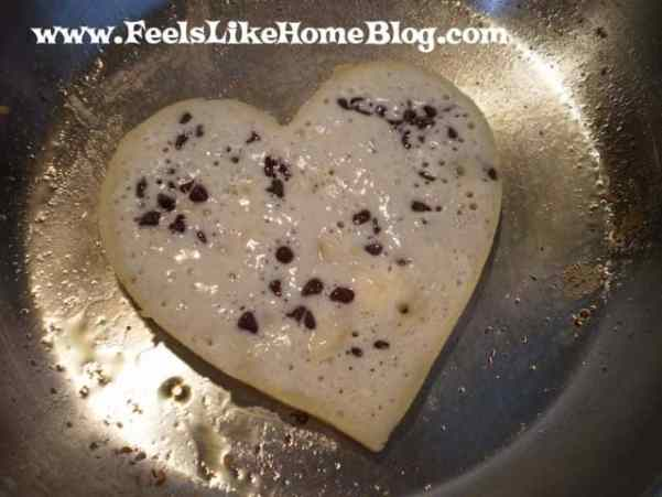 A pancake cooking with hearts