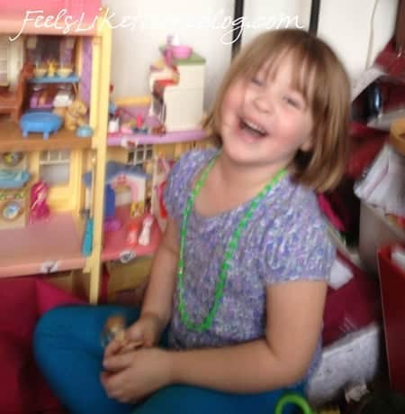 A little girl sitting in front of a dollhouse