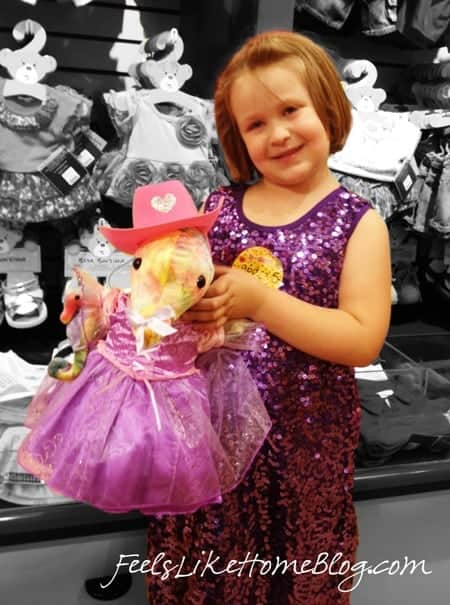 A little girl with her new stuffed animal at her Build A Bear Workshop birthday party