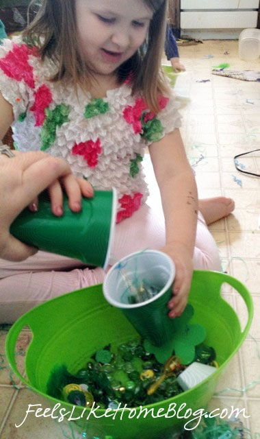 A little girl pouring objects into a cup