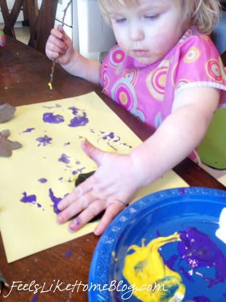 A little girl sitting at a table with a plate of paint