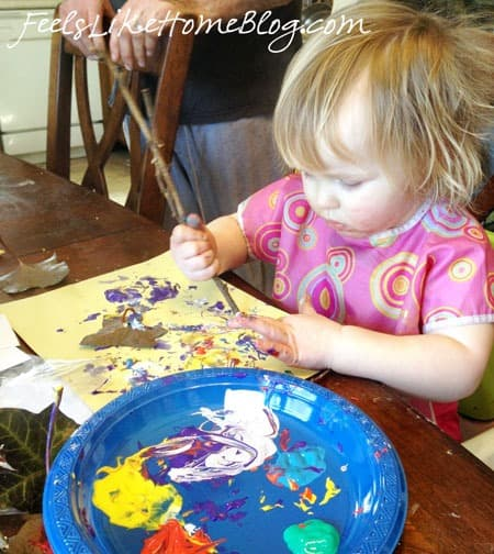 A little girl sitting at a table with a stick and paint