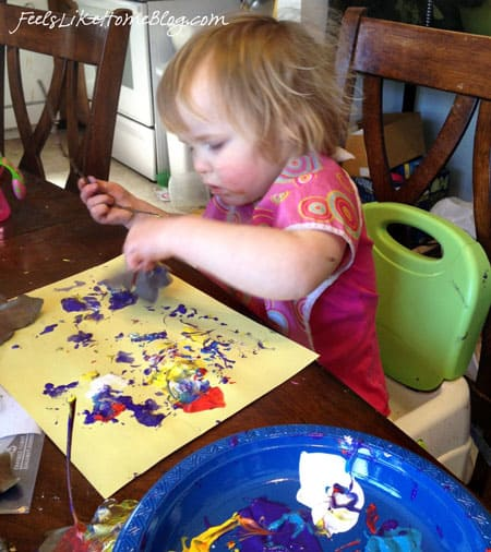 A little girl using a leaf as a stamp in paint