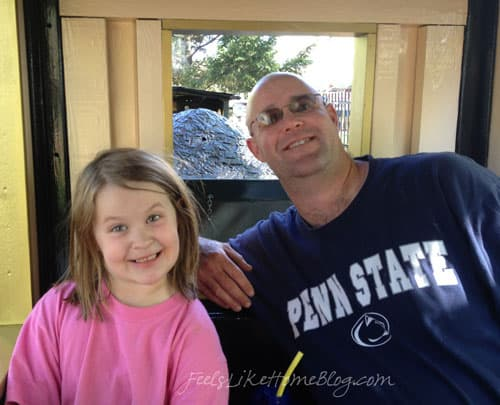 A man and a little girl posing in a train car