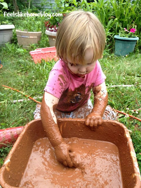 A small child playing in a pan of mud