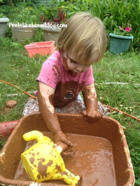 A little girl filling a watering can with mud