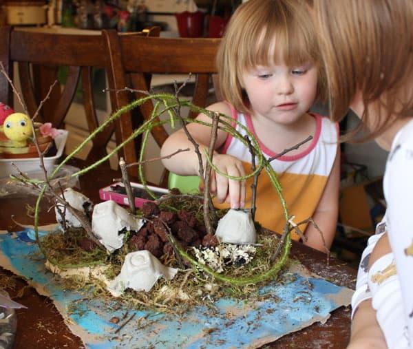 A small child adding rocks to her island
