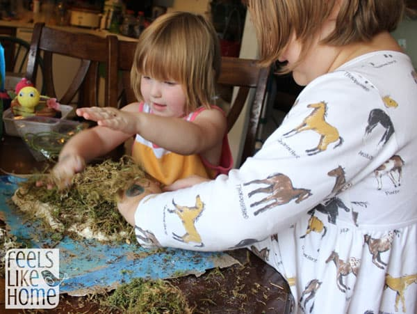 Young children adding moss to their island