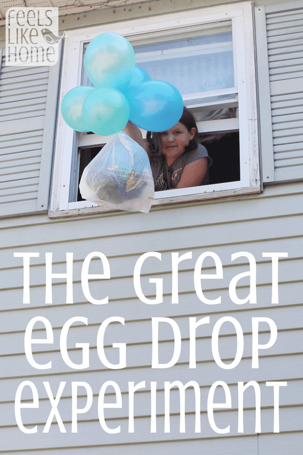 A kid hanging out a window with an egg drop experiment