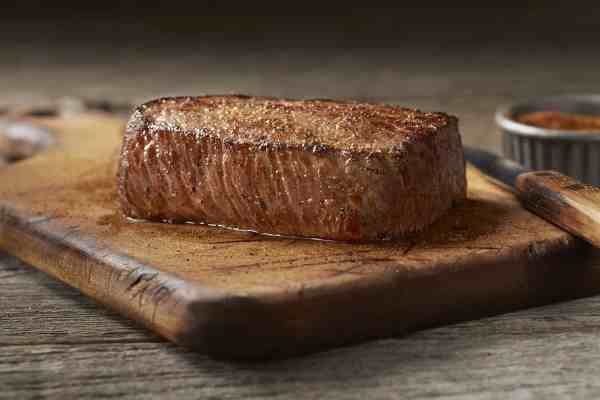 A piece of steak sitting on top of a wooden cutting board