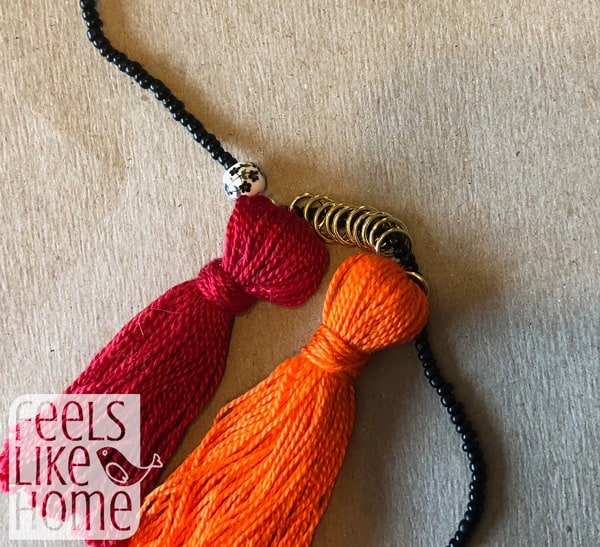 Attach the jump rings to the beaded cord with more jump rings in between the tassels