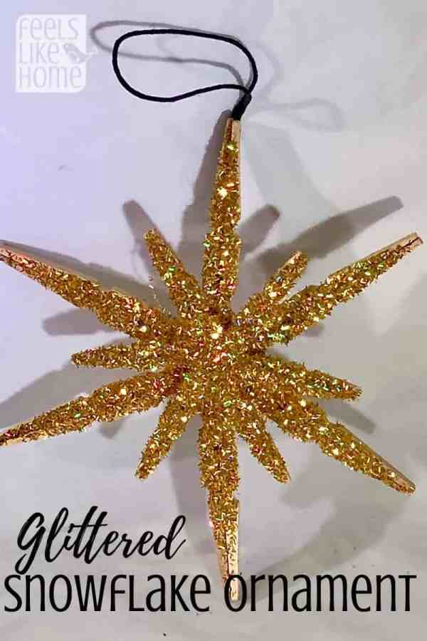 A clothespin snowflake all covered in glitter