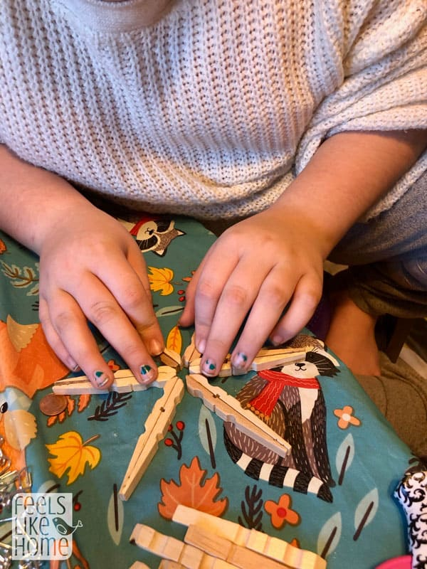 a girl glueing clothespins together